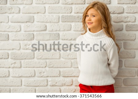 Portrait of a pretty little blonde girl looking in camera and smiling while standing against white brick wall - stock photo