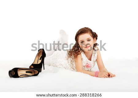 Portrait of a pretty little fun fashion girl lying on a fluffy rug on the floor against white background - stock photo