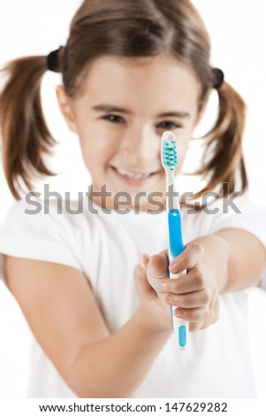 portrait of a pretty Little girl holding a toothbrush - stock photo