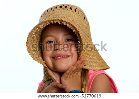 Portrait of a pretty little girl wearing a straw hat and pulling it over her ears