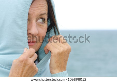 Portrait of a pretty looking mature woman wearing a hooded jumper covering her head, with half her face, with relaxed and happy expression, blurred background of ocean and bright sky as copy space. - stock photo