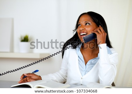 Portrait of a pretty lovely young woman smiling and looking up while is on phone at home indoor