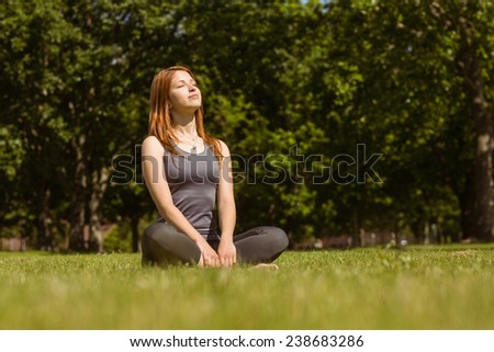 Portrait of a pretty redhead sitting carefree in sunshine - stock photo