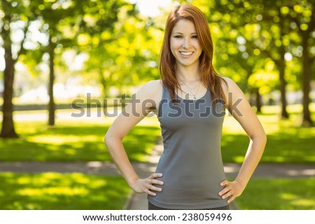Portrait of a pretty redhead smiling on a sunny day - stock photo