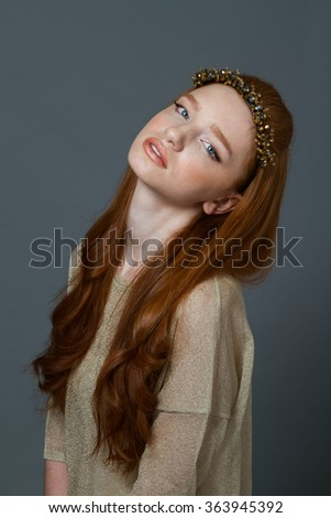 Portrait of a pretty redhead woman with hoop on her head looking at camera over gray background - stock photo