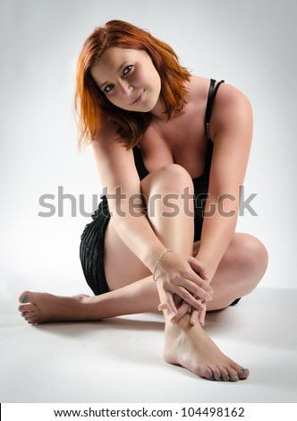 Portrait of a pretty redheaded woman sitting on the floor - stock photo