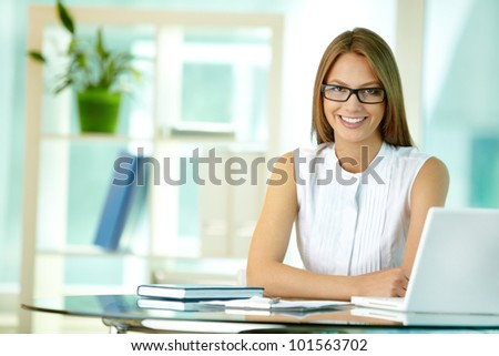Portrait of a pretty secretary sitting at her desk and smiling - stock photo