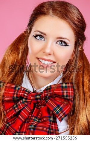 Portrait of a pretty smiling teen girl in school uniform posing over pink background. Anime style.  - stock photo