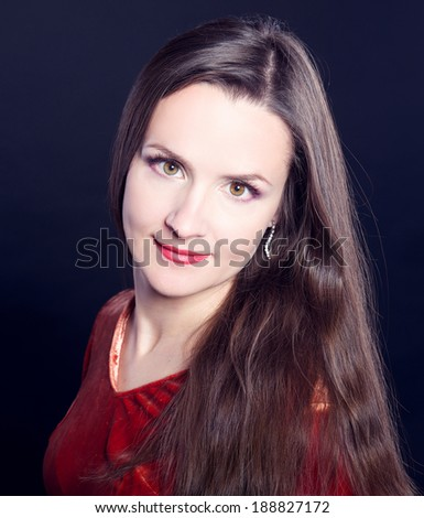 Portrait of a pretty smiling young woman. Black studio background