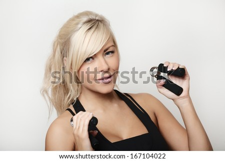 portrait of a pretty sporty woman shot in the studio using hand grip strengthener - stock photo
