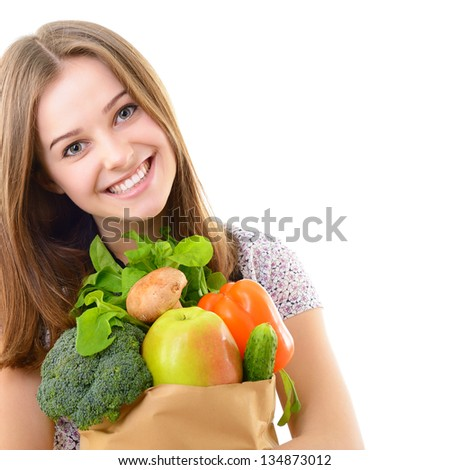 Portrait of a pretty teen girl holding a grocery bag and smiling against white background - stock photo