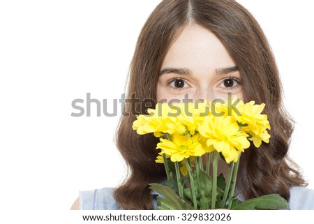 Portrait of a pretty teenage brunette girl posing hiding behind a bunch of yellow flowers smiling with her eyes, isolated on white background - stock photo