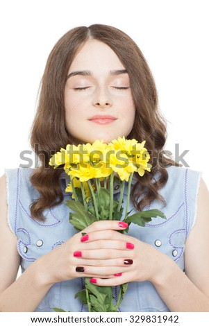 Portrait of a pretty teenage brunette girl posing holding a bunch of yellow flowers smelling them with her eyes closed, isolated on white background - stock photo