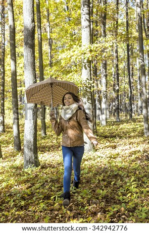 Portrait of a pretty teenage girl with an umbrella running in the forest - stock photo