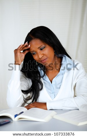 Portrait of a pretty tired young black female learning with headache - stock photo