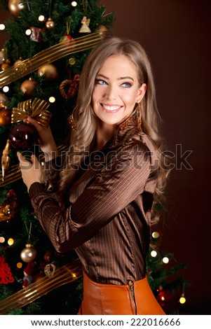 Portrait of a pretty woman decorating the Christmas tree - stock photo