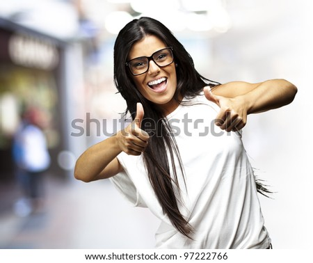 portrait of a pretty woman doing an approve symbol at a crowded place - stock photo