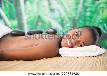 Portrait of a pretty woman enjoying a hot stone massage at the health spa - stock photo
