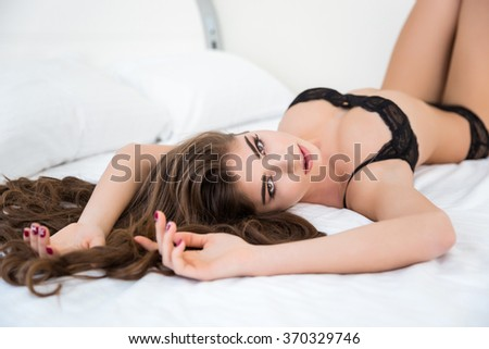 Portrait of a pretty woman in sexy lingerie lying on the bed and looking at camera - stock photo