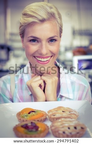 Portrait of a pretty woman looking at a fruit pie at the bakery - stock photo