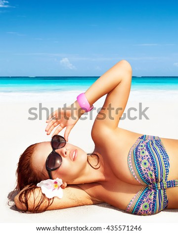 Portrait of a pretty woman on the beach, wearing sunglasses, lying down on clean white sandy coast, enjoying day spa on a tropical resort, luxury summer vacation - stock photo