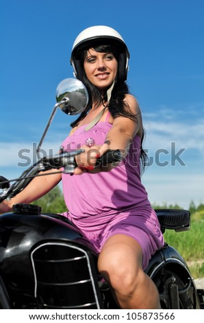 Portrait of a pretty woman riding a motorcycle. - stock photo