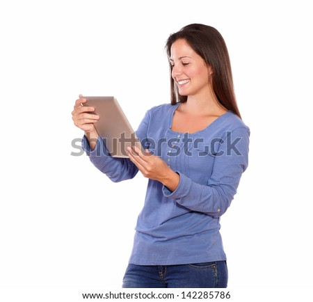 Portrait of a pretty woman working on tablet pc while standing on white background