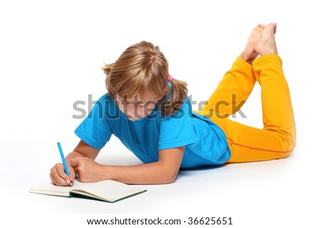 Portrait of a pretty writing girl with opened book. - stock photo