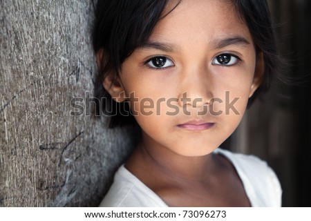 Portrait of a pretty 8 year old Filipina girl in poverty-stricken neighborhood, natural light. - stock photo