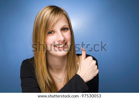 Portrait of a pretty young blond woman showing big thumbs up.