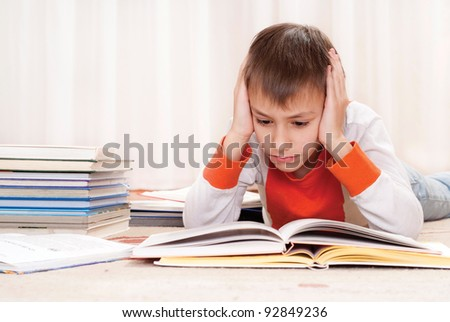 portrait of a pretty young boy with books