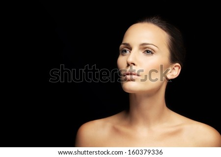 Portrait of a pretty young brunette looking away at copyspace. Beautiful woman with clean and glowing skin isolated on black background - stock photo