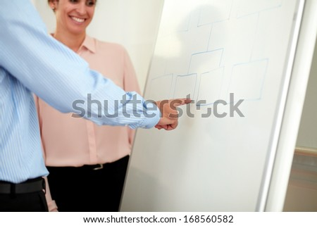 Portrait of a pretty young businesswoman on pink shirt looking at whiteboard with colleagues - copyspace - stock photo