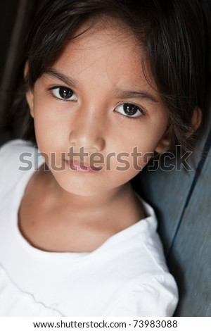 Portrait of a pretty young girl from the Philippines against a wall - stock photo