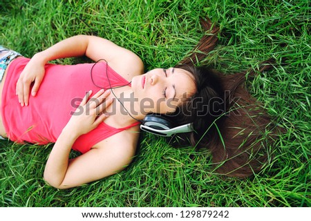 Portrait of a pretty young girl listening music. - stock photo