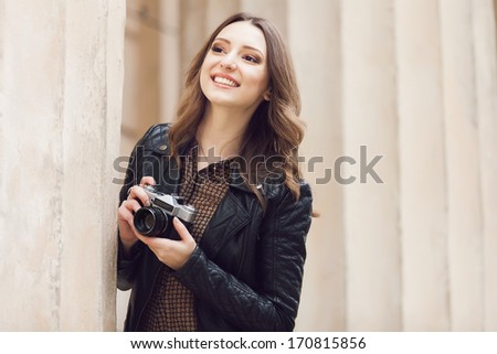 Portrait of a pretty young tourist taking photographs with vintage retro camera - stock photo