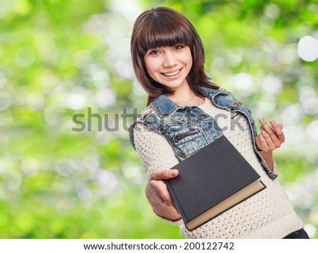 portrait of a pretty young woman giving a book