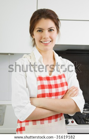Portrait of a pretty young woman in the kitchen - stock photo