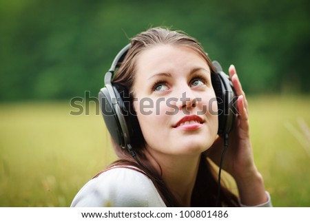 portrait of a pretty young woman listening to music on her mp3 player outdoors (daydreaming) - stock photo