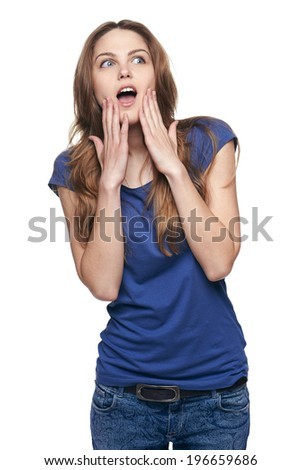 Portrait of a pretty young woman putting her hands to her face in surprise, looking up - stock photo