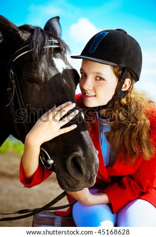 portrait of a pretty young woman riding a black horse