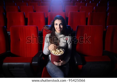 portrait of a pretty young woman sitting in an empty theater, she eats popcorn and smiles, front view