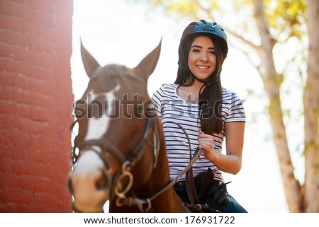 Portrait of a pretty young woman taking a ride with her horse on a sunny day