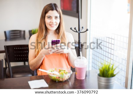 Portrait of a pretty young woman updating her social media status while eating some healthy food at a restaurant - stock photo