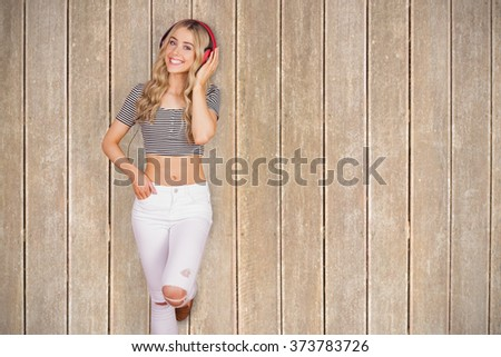 Portrait of a pretty young woman with headphones against wooden planks - stock photo