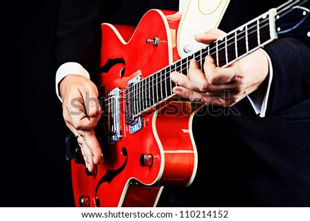 Portrait of a professional artist playing his guitar. Over black background. - stock photo