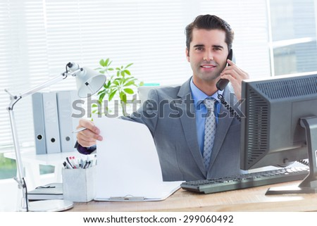 Portrait of a professional businessman checking at his notebook while on the phone - stock photo