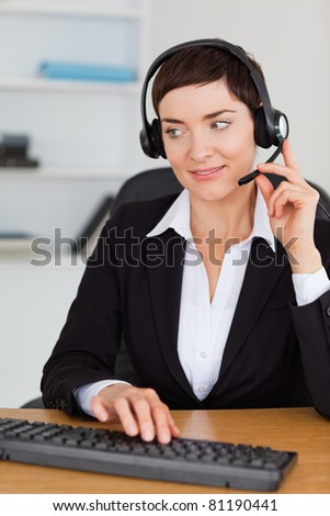 Portrait of a professional secretary calling with a headset in her office - stock photo