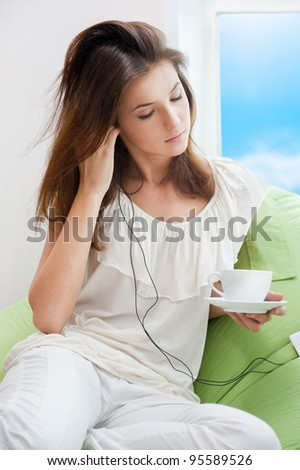 Portrait of a quiet woman enjoying some music in her bedroom