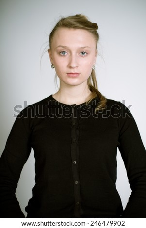 Portrait of a real young woman on a light background in a black cardigan. Shallow depth of field. Focus on the eyelashes - stock photo